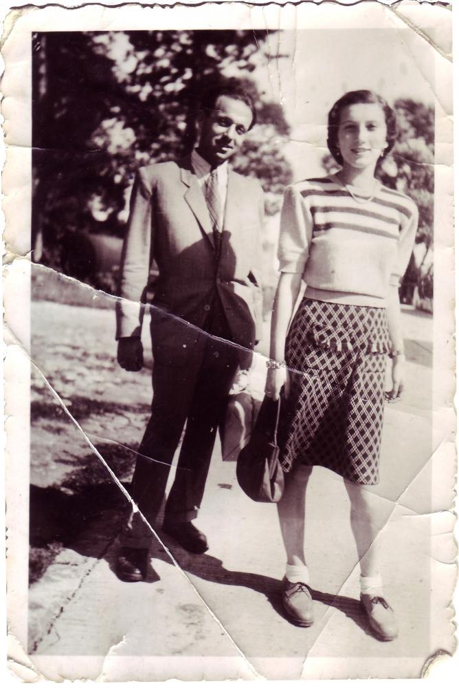 Photo en noir et blanc d'un homme et d'une femme debout sur une allée pavée à l'extérieur. Il y a des arbres en arrière-pplan. L'homme porte un complet et la femme porte une blouse et une jupe à pois.
