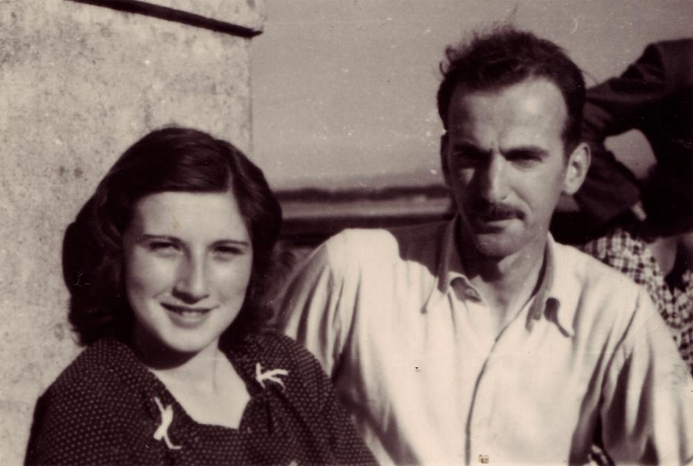 Photo en noir et blanc d'un homme et d'une femme, assis ensemble à l'extérieur. La femme a de cheveux bruns jusqu'aux épaules et l'homme porte une moustache ainsi qu'une chemise à col de couleur pâle.