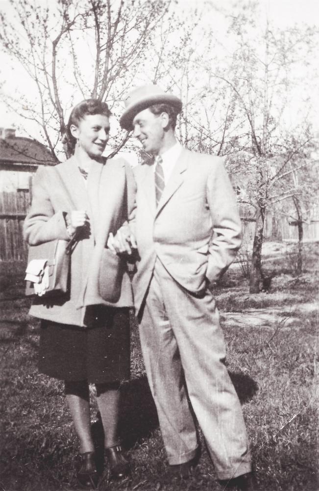 Photo en noir et blanc d'un homme et d'une femme, bras-dessus bras-dessous, sur un terrain extérieur avec des arbres en arrière-plan. Le couple se sourit l'un à l'autre et l'homme porte un complet et un chapeau.