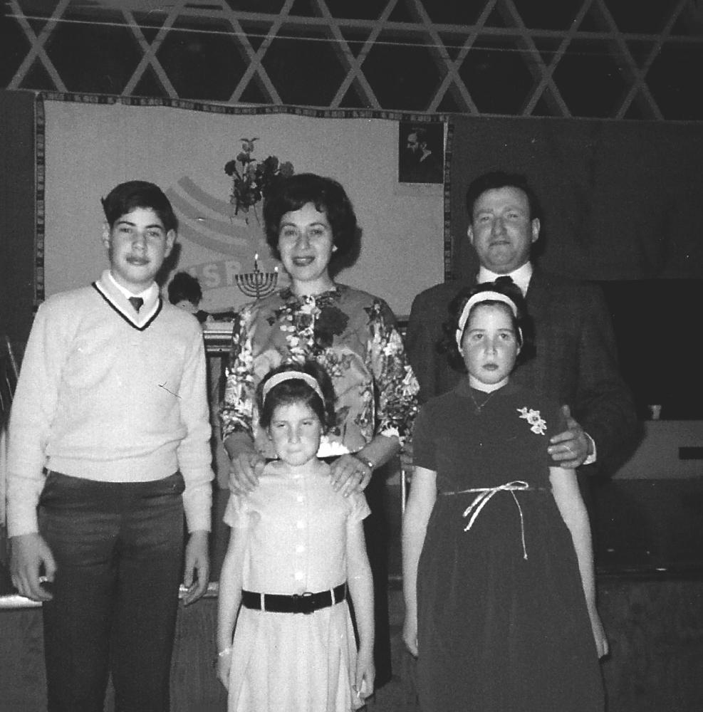 Photo en noir et blanc d'une famille de cinq, à l'intérieur, debout et souriant. La famille inclus un homme et une femme avec leur adolescent et leurs deux jeunes filles. Il y une menorah en arrière-plan.