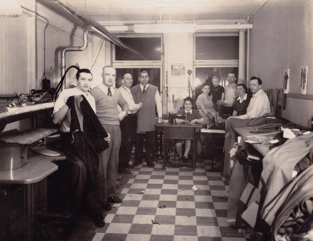 Photo en noir et blanc d'un groupe d'environ dix personnes debout ou assises ensemble dans une salle dans laquelle il y a deux fenêtres au fond. Le groupe regarde la caméra. Il y a des piles de tissus et de vêtements à droite et le plancher est à motif de damiers.