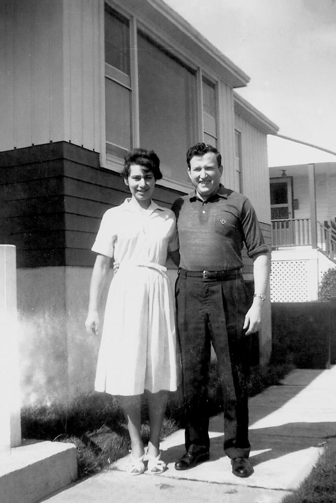 Photo en noir et blanc d'un homme et d'une femme souriant et se tenant debout dans l'allée à l'extérieur d'une maison. Il semble que ce soit l'été. La femme porte une robe à manches courtes.