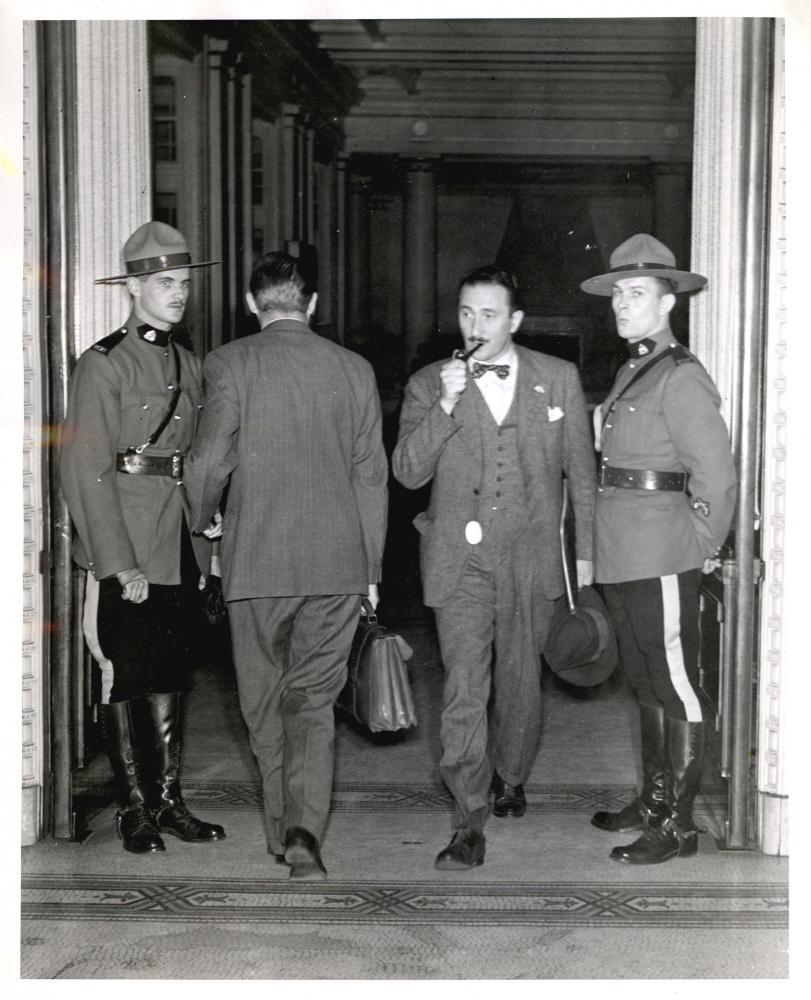 Photo en noir et blanc de quatre hommes dans une grande porte. Un homme, le deuxième à partir de la droite, sort de la pièce avec un attaché-case et a une pipe dans sa bouche. L'homme à sa gauche entre dans la pièce. Les deux hommes se tenant de part et d'autre portent un uniforme de la Gendarmerie royale du Canada et regardent en direction de la caméra.