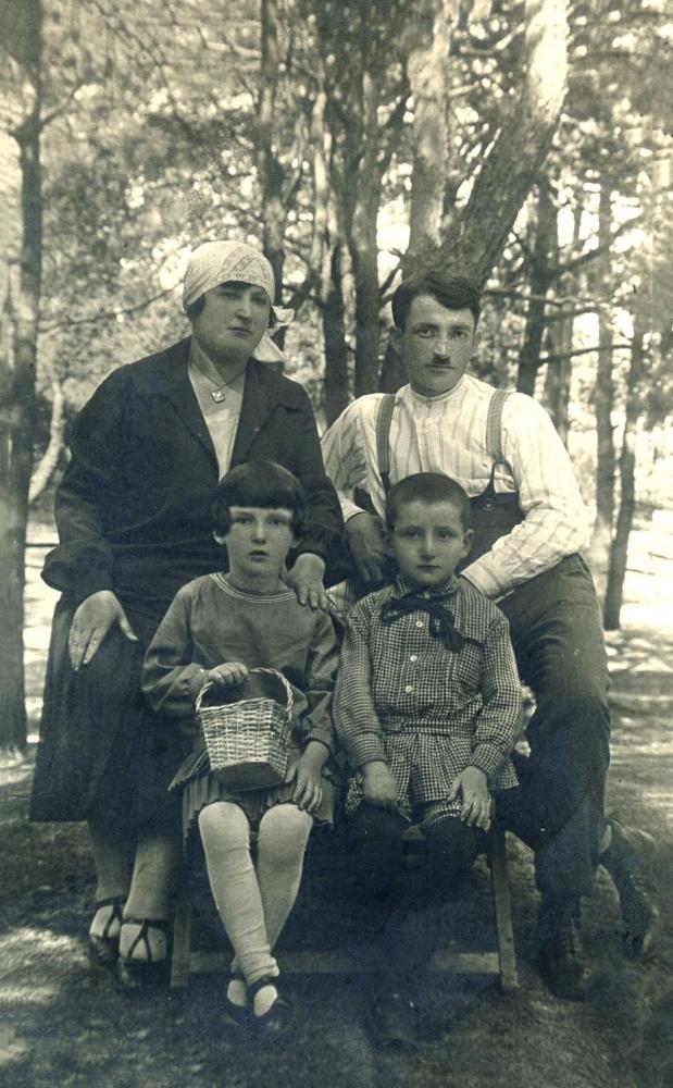 Photo en noir et blanc d'une famille de quatre, rassemblés ensemble pour une photo extérieure, entourés d'arbres. L'homme et la femme se tiennent derrière leur deux enfants assis.