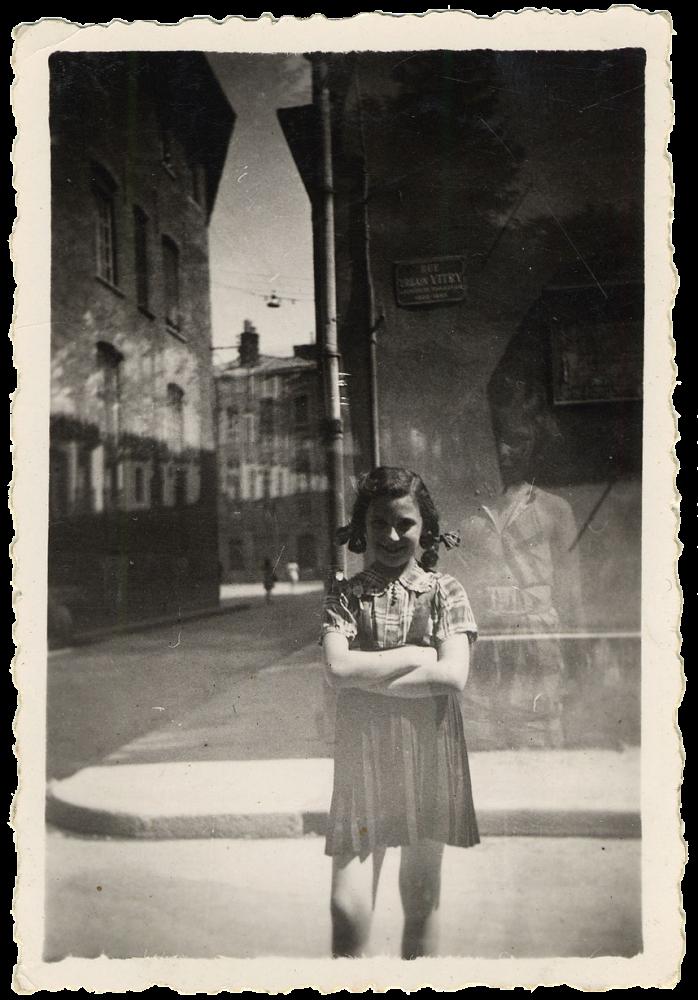 Photo en noir et blanc d'une jeune fille se tenant dans une rue debout les bras croisés. Elle se tient près du coin de la rue, la route et le trottoir continue en arrière-plan.