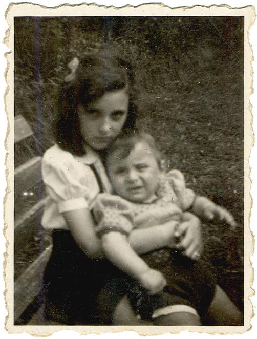 Photo en noir et blanc d'une fille assise sur un banc, tenant un jeune enfant sur les genoux. La fille a une boucle dans les cheveux. Les deux enfants regardent la caméra sans sourire.