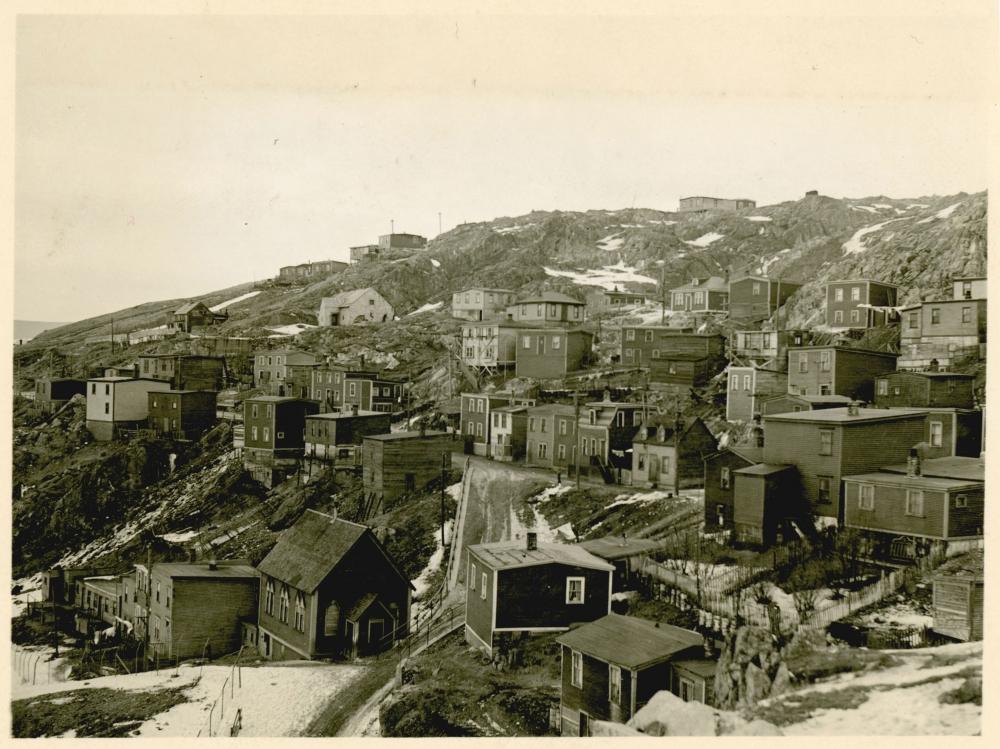 Photo en noir et blanc de petits bâtiments résidentiels dans un village ou une ville bâti sur une colline. Il y a de la neige au sol et il semble que ce soit l'hiver.