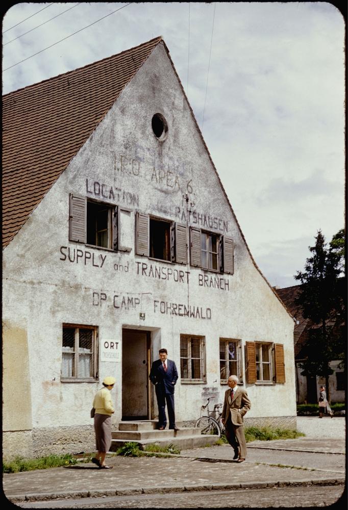 Diapositive en couleur d'une vue extérieure d'un bâtiment de trois étages. Trois hommes se tiennent devant le bâtiments.