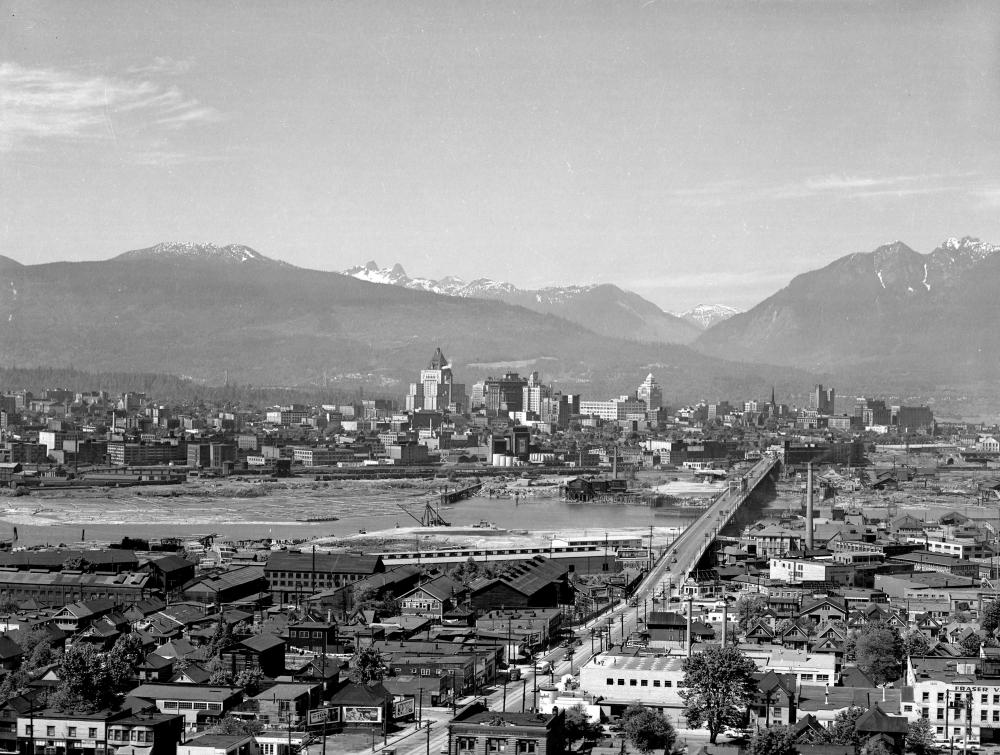 Photo en noir et blanc, vue aérienne d'une ville. Plusieurs bâtiments sont répartis de part et d'autre d'une rivière. Un pont reliant les deux rives se trouve dans la partie droite de la photo. Plusieurs sommets montagneux sont visibles à l'arrière-plan.