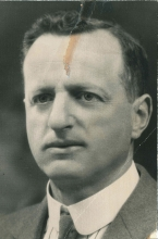 Black-and-white portrait photograph of a man, photo taken from his shoulders up. He is wearing a suit and tie.