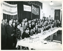 Black-and-white photograph of a large group of approximately 70 people smiling for a group photograph in a room. The group poses behind a large table with food and dishes on it, and there are two flags hung on curtains in the background.