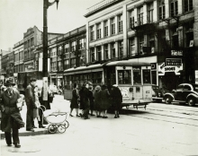 Black-and-white photograph of a street scene, taken from street level. A group of people are waiting to board a streetcar, parked on the street.