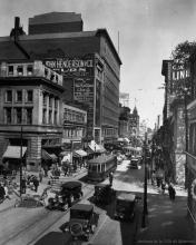Photographie en noir et blanc d'une scène d'une rue achalandée où circulent des voitures d'époque et des tramways. Des piétons marchent dans chaque direction sur des trottoirs et il y a des panneaux d'affichage publicitaire sur les murs extérieurs des édifices.
