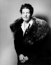 Photo en noir et blanc d'un portrait de femme à partir de la taille. Elle porte un manteau noir avec un col de fourrure. Ses cheveux sont courts et frisés et elle regarde directement la caméra.