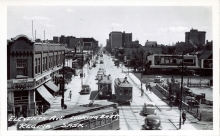 Black-and-white photograph of a street scene, taken from a high vantage point. The large street has pedestrians on the sidewalks, storefronts on either side, and three streetcars driving along in the middle of the road.