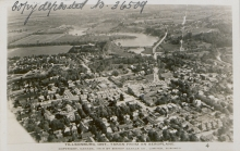 Black-and-white aerial photograph of a town with a river visible in the distance. Text has been handwritten in the top-left corner of the photograph.