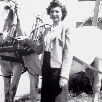 Black-and-white photograph of woman with dark brown hair, standing outdoors beside two white horses tied up to a carriage or wagon. She rests one of her hands on the horse's reins.