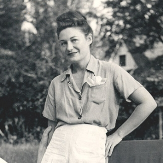 Black and white photo of a woman standing in a garden. She wears shorts and summer clothes.