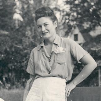 Photo en noir et blanc d'une femme debout dans un jardin. Elle porte des shorts et des vêtements estivaux.