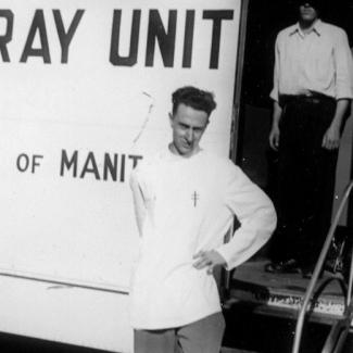 """Photo en noir et blanc d'un homme debout, la main appuyée sur la hanche gauche, devant un grand camion blanc sur lequel il est inscrit """"X-RAY UNIT"""" sur un côté. Un homme est debout derrière lu dans l'entrée du camion, son visage est caché par un ombrage."""