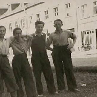 Photo en noir et blanc d'un groupe de quatre garçons se tenant bras-dessus bras-dessous sur la partie ombragée d'une route. Il y a un grand édifice de l'autre côté de la rue.
