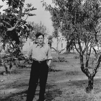 Photo en noir et blanc d'un jeune homme se tenant debout sur une pelouse, avec un arbre de chaque côté de lui.