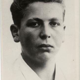 Portrait photographique d'un jeune homme, âgé d'environ 15 ans. Le jeune homme porte un chemise blanche à col et a les cheveux coiffés vers l'arrière. Il regarde directement la caméra et ne sourit pas.