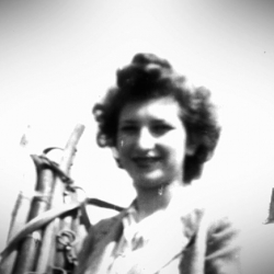 Black-and-white photograph of a woman smiling at the camera, standing beside a white horse with her hand resting on the horse's reigns.
