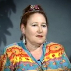 Screenshot of Holocaust survivor Helene Goldflus video testimony. She is sitting in front of a blue wall with a plant in the background, and looking to the right of the camera. The camera shows her face and shoulders.