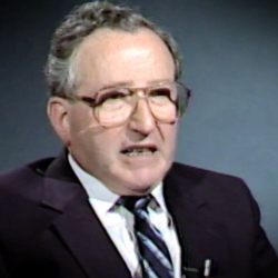 Screenshot of Holocaust survivor Moishe Kantorowitz video testimony. He is sitting in front of a dark background, and looking to the left of the camera. The camera shows his face and shoulders.