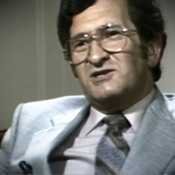 Screenshot of Holocaust survivor David Mark testimony video. He is sitting in front of a grey background, and looking to the left of the camera. The camera shows his face and shoulders.