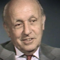 Screenshot of Holocaust survivor George Lysy video testimony. He is sitting in front of a grey background, and looking to the left of the camera. The camera shows his face and shoulders.