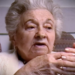 Screenshot of Holocaust survivor Mania Kay video testimony. She is sitting in front of a black background, and looking to the right of the camera. The camera shows her face and shoulders.