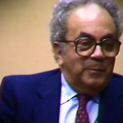 Screenshot of Holocaust survivor David Shafran video testimony. He is sitting in front of a beige background, and looking to the right of the camera. The camera shows his face and shoulders.
