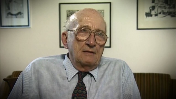 Screenshot of Holocaust survivor Gerhart Maass video testimony. He is sitting in front of a wall with three paintings, and looking to the right of the camera. The camera shows his face and shoulders.