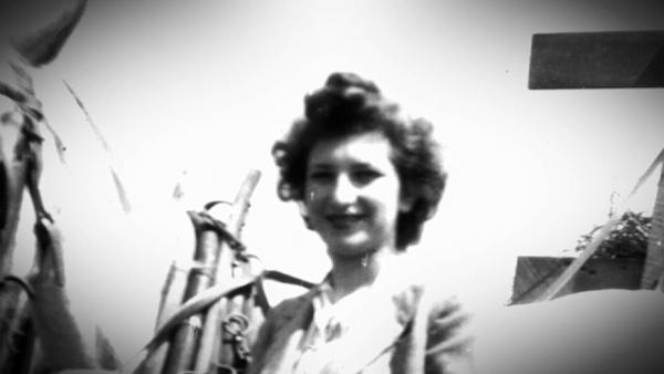 Photo en noir et blanc d'une femme, Minna Loewith, debout à cöté de son cheval blanc, avec sa main tenant les rênes.