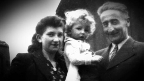 Photo en noir et blanc d'une femme, Minna Loewith, debout à côté un homme qui tient dans ses bras un garçon avec des cheveux blonds bouclés.