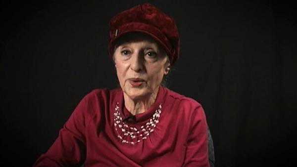 Capture d'écran du témoignage vidéo de  la survivante de l'Holocauste Sarah Engelhard, assise devant un fond noir, et regardant à la gauche de la caméra. Son visage et ses épaules sont visibles à la caméra.