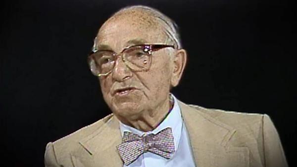 Capture d'écran du témoignage vidéo du survivant de l'Holocauste Joseph Klinghoffer, assis devant un fond noir, et regardant à la gauche de la caméra. Son visage et ses épaules sont visibles à la caméra.