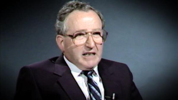 Capture d'écran du témoignage vidéo du survivant de l'Holocauste Moishe Kantorowitz, assis devant un fond noir, et regardant à la gauche de la caméra. Son visage et ses épaules sont visibles à la caméra.