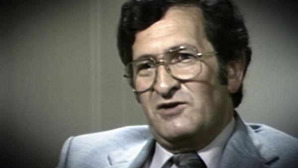 Capture d'écran du survivant de l'Holocauste David Mark, assis devant un fond gris, et regardant à la gauche de la caméra. Son visage et ses épaules sont visibles à la caméra.