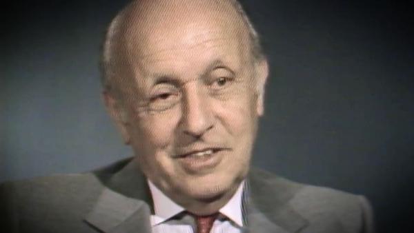 Capture d'écran du témoignage vidéo du survivant de l'Holocauste George Lysy, assis devant un fond gris, et regardant à la gauche de la caméra. Son visage et ses épaules sont visibles à la caméra.