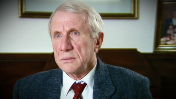 Screenshot of Holocaust survivor Elliott Zuckier video testimony, sitting in his living room, and looking to the left of the camera. The camera shows his face and shoulders.